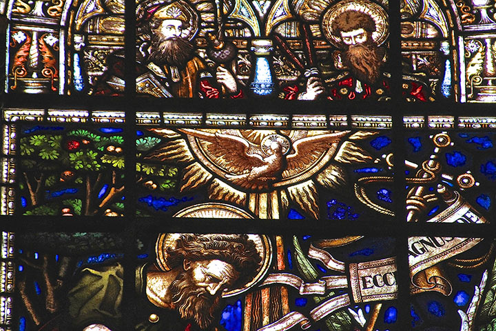Detail of a stained glass window at Trinity with dove ascending.