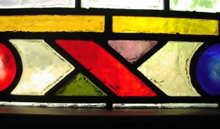 Stained Glass in yellow, red, green, blue and lavender arranged in a geometric pattern with black lines between each piece of glass. The dominant feature is an 'X' in the middle, made of glass, with a red downstroke and green and lavender behind.