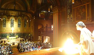 The Rev. Rainey Dankel stands over the Easter vigil fire on the West balcony. Below we can see the faces of the congregation.