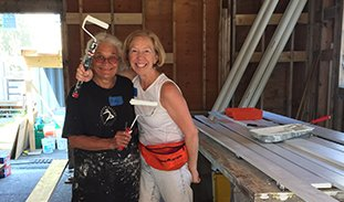 Two members of the Habitat for Humanity team pose with paint rollers.