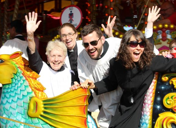 Choir members ride a carousel.