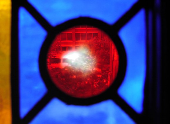 Stained glass in cobalt blue, goldem orange, and red. There is a red circle surrounded by four blue almost triangles, with an orange bar on the left-hand side.