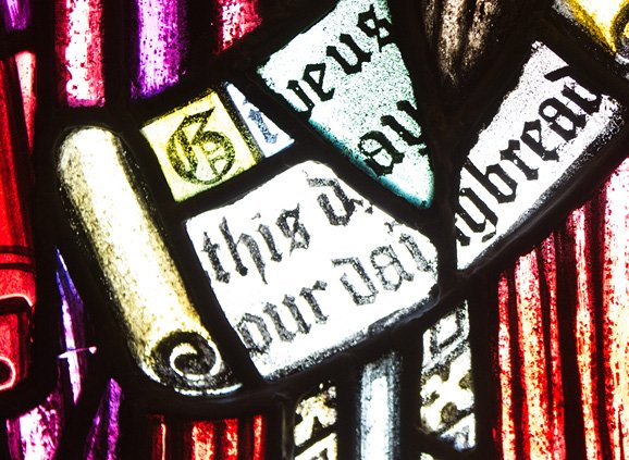 purple, red, and white stained glass depicting a scroll. The scroll reads in Gutenberg-style text: 'Give us this day our daily bread'