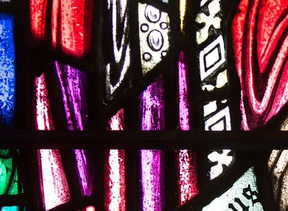 Colorful stained glass that looks like folds of cloth in cobalt blue, violet, and red, with patterned black and white blocks breaking up the space about two-thirds of the way into the image.