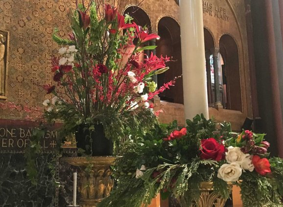 Red flowers and greenery in vases on Trinity's altar