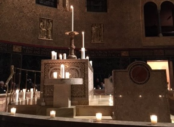 Trinity's Chancel and altar lit by votive candles.