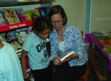 Trinity parishioner shares a book with a student at Dever Elementary School