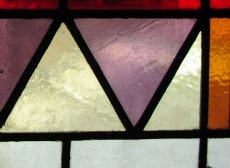 Stained glass in purple, pale green, and red-brown, in a geometric arrangement (mostly triangles)