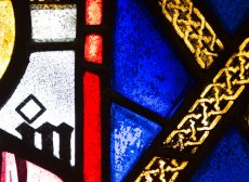 vibrand cobalt blue,cadmium red, and yellos and white stained glass arranged in a geometric pattern. The dominant color is blue.