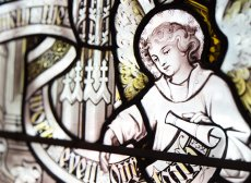 A mostly black & white image of a stained flass window of a winged angel with caucasian features holding a scroll. The legible section of the scroll reads 'even our faith' in a fancy calligraphy hand.
