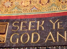 The text 'Seek Ye God' taken from Trinity Church Boston's chancel. The text is inlaid in gold over a polished green stone band, and above the stone is more gold leaf in a repeating circle pattern.