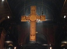 The Trinity cross lit from behind in a dark church, viewed from the back of the chancel.