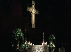 The cross and altar lit by candlelight.