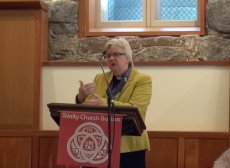 The Very Rev. June Osborne speaking at the podium in the Forum.