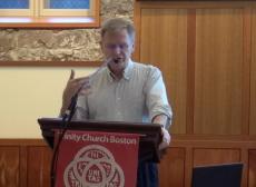 Mark Jordan speaks at a podium in the Forum of Trinity Church Boston
