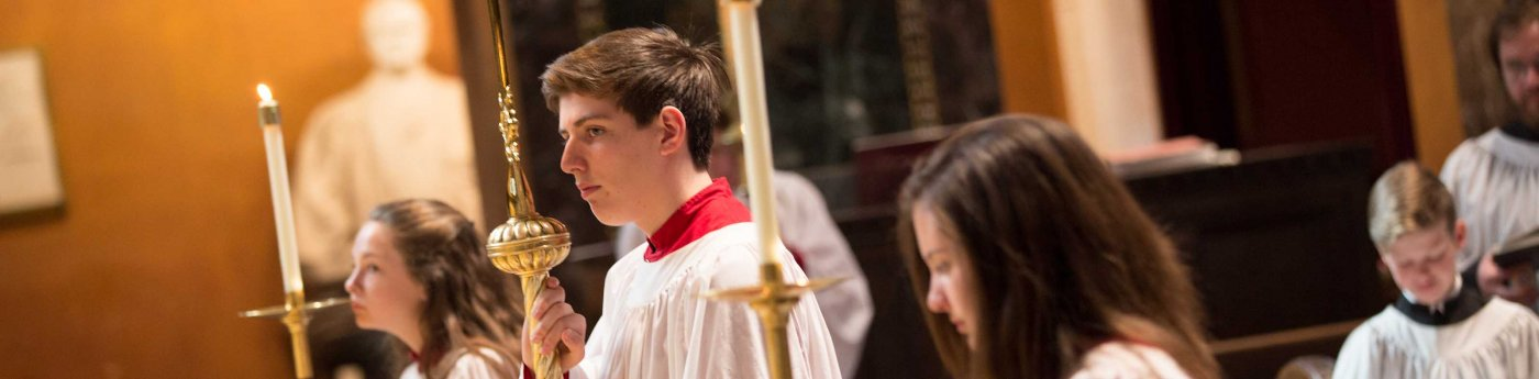Acolytes carry torches and candles during a service.
